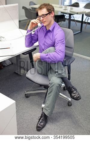 caucasian man office worker with phone in hand, stretching legs , exercising during work  in his office