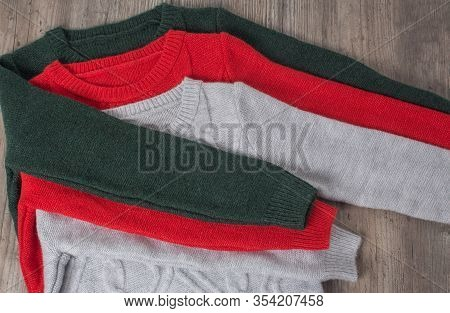 Clothing, Fashion, Style. Multicolored Sweaters Are Placed On A Wooden Table. The Clothes Are Neatly