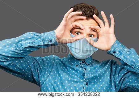 Sick Guy Looking At The Camera With A Surprised Medical Mask. Virus Protection During Influenza Epid
