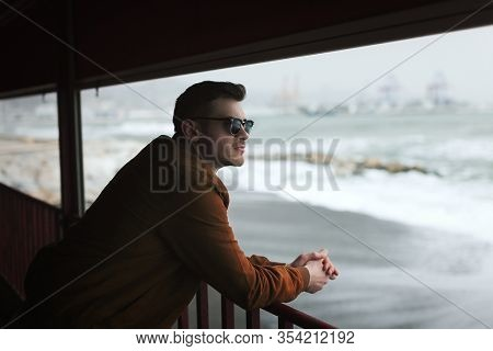 View of an young man leaning on the railing in front of the beach