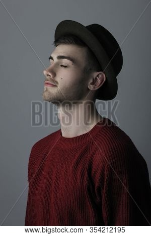 Portrait of a young man with closed eyes standing against grey background