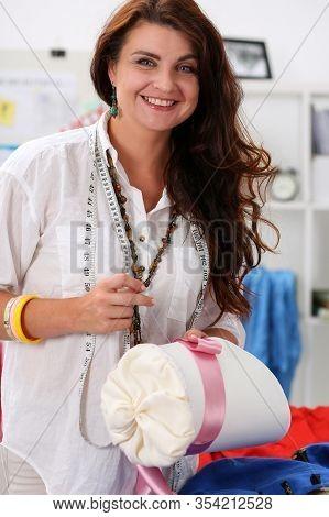 Female Seamstress Sews Silk Ribbon To Female Hat. Performing Professional Manual Work In Creative Wo