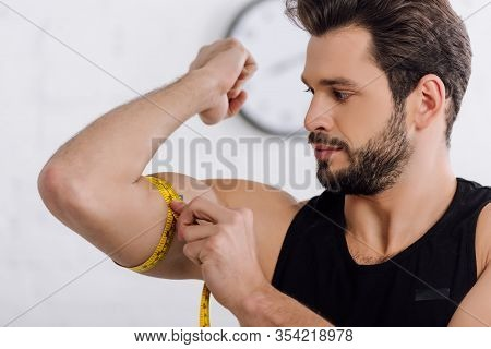 Handsome And Sportive Man Measuring Muscle On Hand