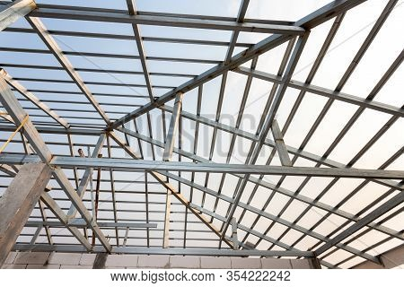 Structure Of Steel Roof Frame For Home Construction. Concept Of Residential Building Under Construct