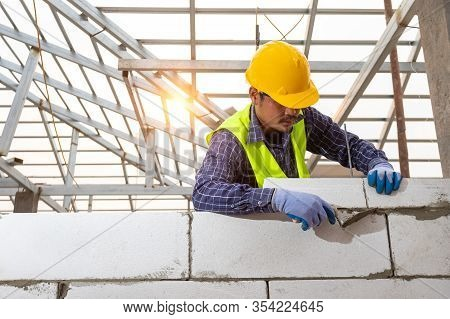 Bricklayer Builder Working With Autoclaved Aerated Concrete Blocks. Walling, Installing Bricks On Co