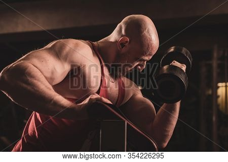 Bald Cute Man With A Beard Is Doing Biceps Exercise. The Young Guy Is Engaged In Bodybuilding. Train