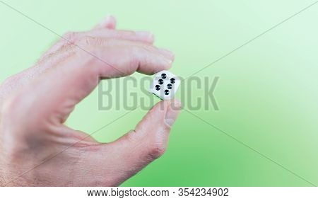 Close Up Of Hand Holding Dice Showing Showing Six Pips Against Green Background