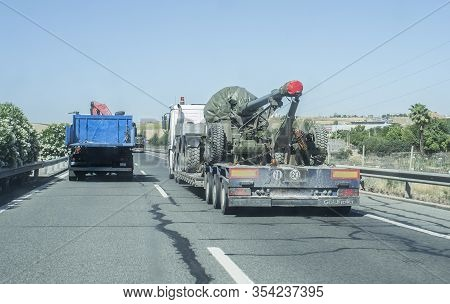 Seville; Spain - May 31st, 2019: Heavy-duty Truck Carrying Big Army Weapon. Road Convoy With Militar