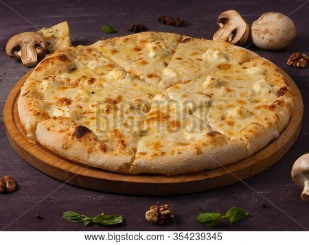 Pizza Quattro Fromaggi On A Wooden Board