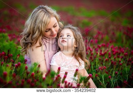 Beautiful Smiling Child Girl With Young Mother In Family Look Clothes In Field Of Clover Flowers In