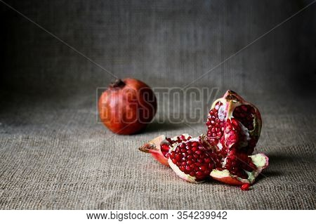 Red Half Pomegranate And Raw Pomegranates On A Brown Sackcloth Background. Rustic Style. Tasty Fruit