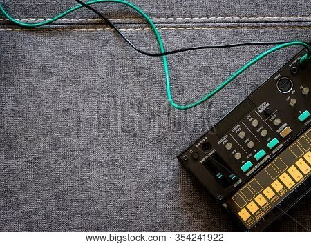 Top View Of Small Black Fm Synthesizer With Patch Cables On Top Of A Sofa With Space To The Left Of