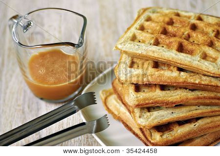 Stack Of Homemade Waffles On The Plate With A Cup Of Brown Syrup