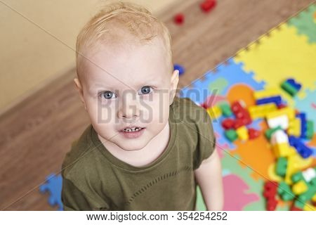 Portrait Of A Happy Smiling Two Year Old Boy On The Background Of Toys.