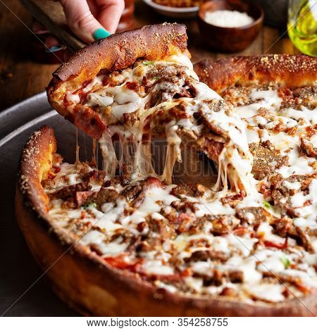 Deep Dish Meat Pizza On A Wooden Table With A Slice Being Pulled