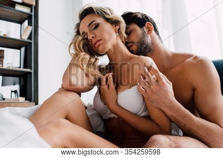 Handsome Man Taking Off Bra Of Sensual Girlfriend On Bed