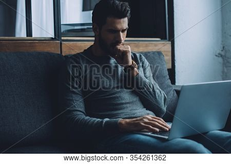 Handsome Man With Hand Near Mouth Watching Pornography On Laptop In Living Room