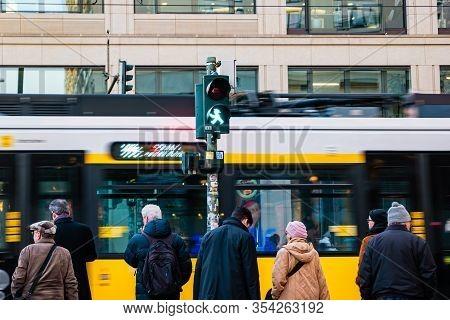 Berlin, Germany - December, 2019: Street Life In Berlin. Pedestrians On Blurred Tram Background.
