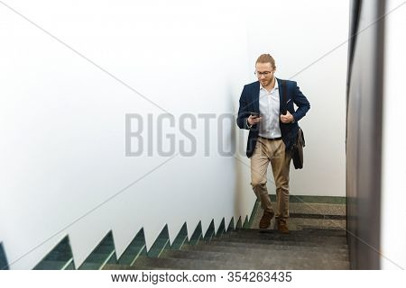 Image of handsome optimistic young businessman indoors walking by upstairs using mobile phone.
