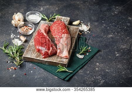 Raw Fresh Steak Sirloin Flap Served With Rosemary, Garlic And On Wooden Cutting Board. Black Angus B