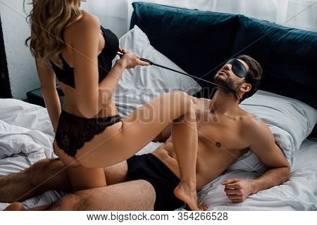 Dominant Woman Holding Flogging Whip Near Submissive Boyfriend In Eye Mask On Bed