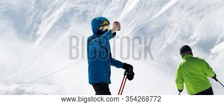 Skier Makes Selfie On Camera Phone And Snow Mountains In Fog At Background. Caucasus Mountains In Wi