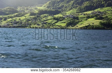 Blue Water Of The Lake Walensee In Switzerland And Green Hills On Lakeshore. Summer Landscape On Sun