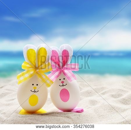 Two Easter Eggs With The Bunny Ears On The Sandy Beach. Easter Concept.