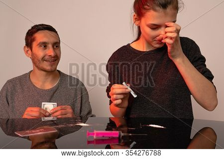 Pleased Junkie Man Holds Banknote In His Hands And Looking At His Girlfriend That Rubs Her Nose Whil