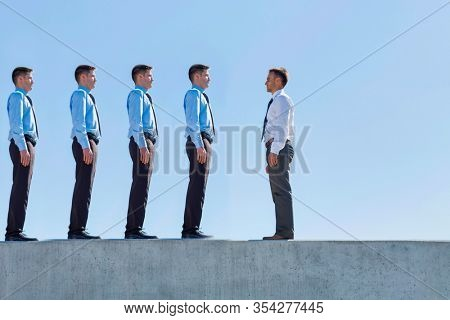 Conceptual photo of a single Businessman standing in office roof top opposite four cloned versions of another businessman