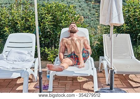 Handsome Bearded Man Sunbathing On Lounge Chair Enjoying With Summertime Poolside Closed Eyes