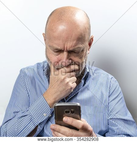 A Middle-aged Man Worried While Talking On A Cell Phone