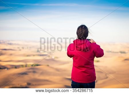 Woman With A Red Jacket Overlooking The Palouse In Washington State