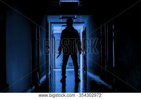 Murder, Kill And People Concept - Criminal Or Murderer Wearing A Mask In Silhouette Holding Knife In