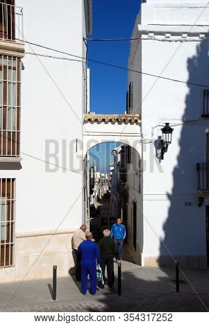 Estepa, Spain - November 13, 2008 - People Walking Through An Archway Leading Off The Plaza Del Carm