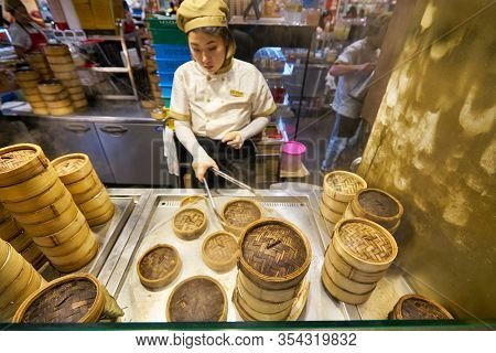 SINGAPORE - JANUARY 20, 2020: bamboo steamers and employee at a food court in the Shoppes at Marina Bay Sands