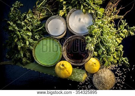 Face Mask For Acne And Blackheads On The Black Wooden Glossy Surface Consisting Of Some Cilantro Lea