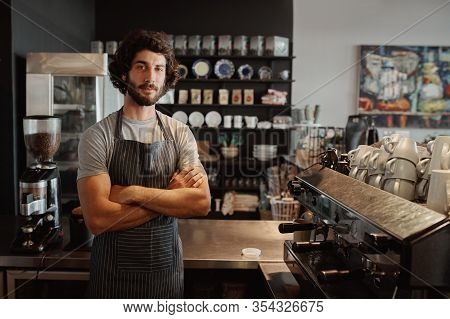 Male Business Owner Behind The Counter Of A Coffee Shop With Folded Hands Looking At Camera