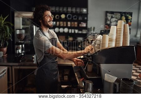 Young Cheerful Barista Wearing Black Apron While Preparing Coffee At An Automatic Machine In A Moder