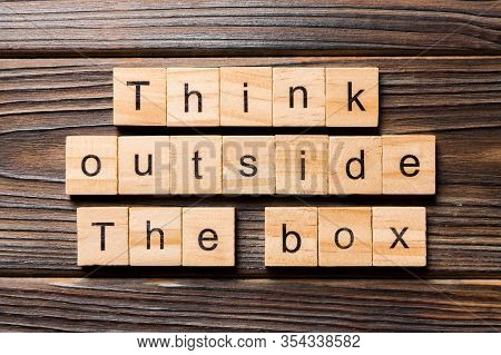 Think Outside The Box Word Written On Wood Block. Think Outside The Box Text On Wooden Table For You