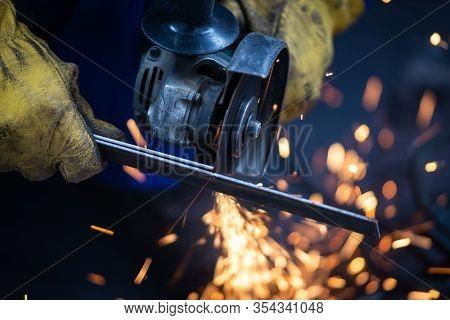 Man Cutting Iron With Grinder At Work. Man Cutting Iron With Circular Grinder. Man Working On Iron W