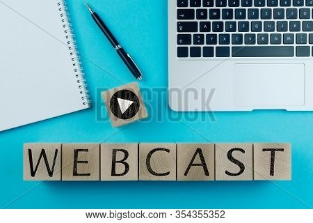 Word Webcast And Play Button Symbol On Wood Cubes Against Blue Background With Laptop And Notepad, W