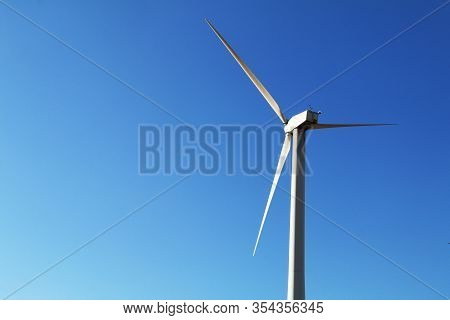 Single Shining White Wind Turbine Bright Blue Sky