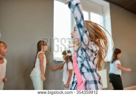 Portrait Of A Little Happy Girl Dancing And Having Fun While Having A Choreography Class. Group Of C