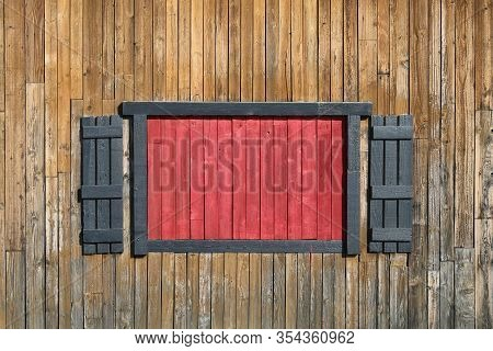 A Bright Red Boarded Pioneer Farm Barn Window With Shutters