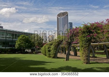 View Of 1 Williams Street Tower And Grand Arbour Structure Covered By Blooming Bouganvillea Flowers