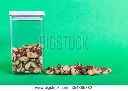 Brazil Nuts Raw Also Called Bertholletia Or Paranoot. They Are In A Transparent Plastic Container Wi