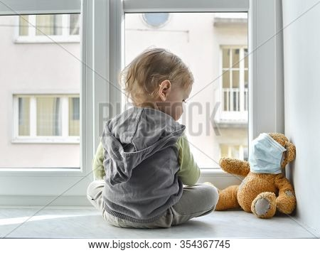 Child In Home Quarantine Standing At The Window With His Sick Teddy Bear Wearing A Medical Mask Agai
