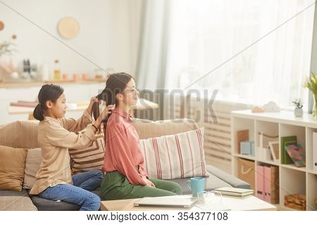Horizontal Side View Shot Of Teen Girl Sittting On Sofa In Cozy Living Room Plaiting Her Mothers Hai