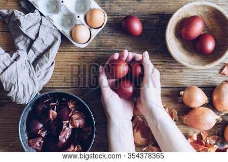 Woman Making Dyed Easter Eggs Painted With Natural Dye Onion On Wooden Background. Process Of Dyeing